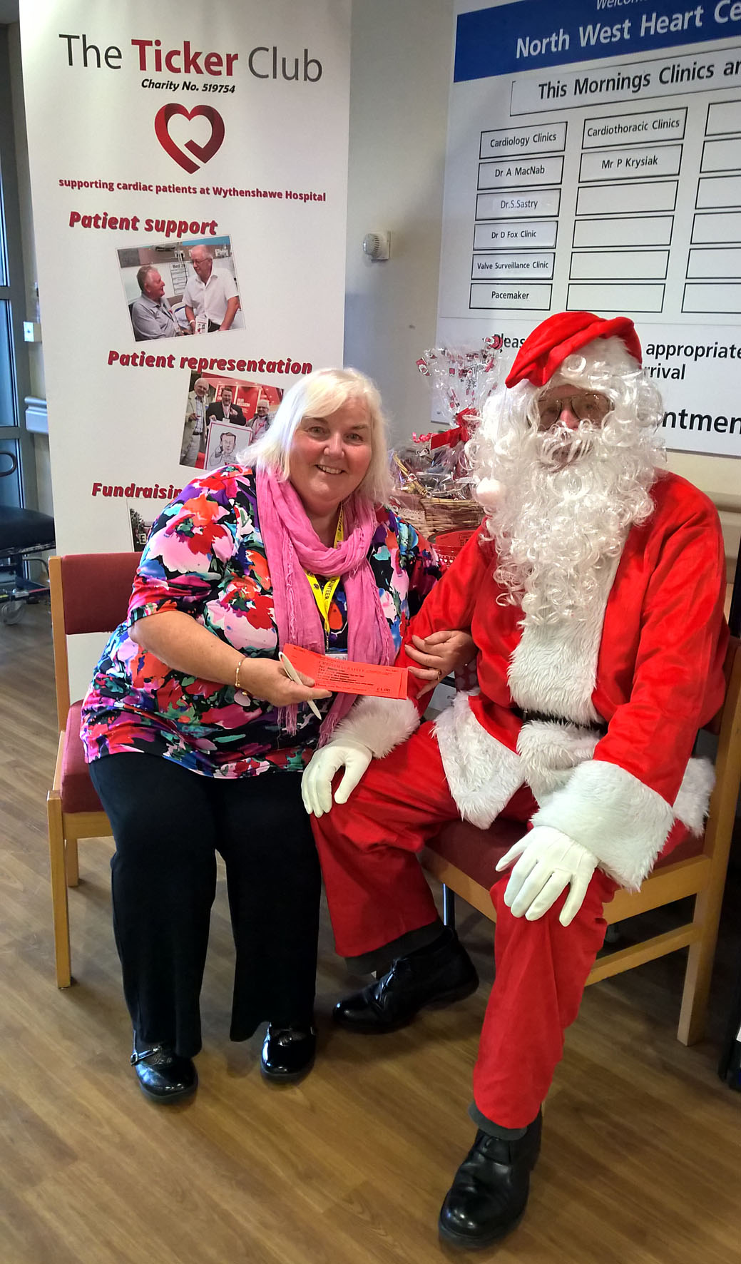 Santa helps sell Barbara Merriman sell Xmas Draw tickets in the NW Heart Centre